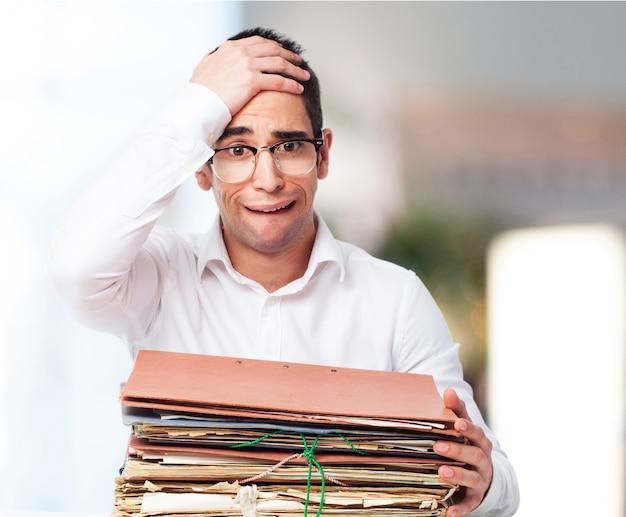 Homme bored regardant une pile de papiers avec une main sur son front Photo gratuit