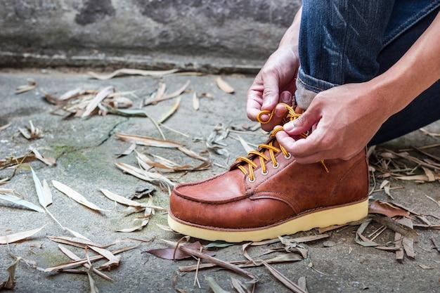 Homme avec des bottes en cuir marron Photo gratuit