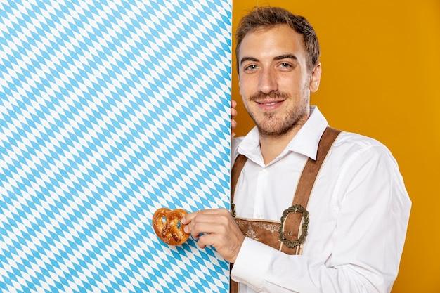 Homme avec bretzel et signe à motifs Photo gratuit