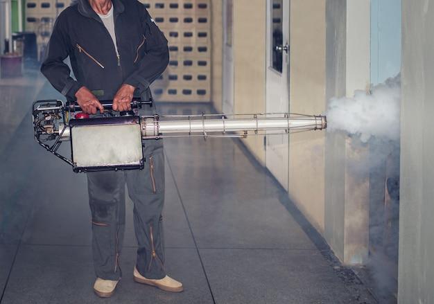 Homme brouillard de pulvérisation, se débarrasser des moustiques pour arrêter la propagation de la dengue Photo Premium