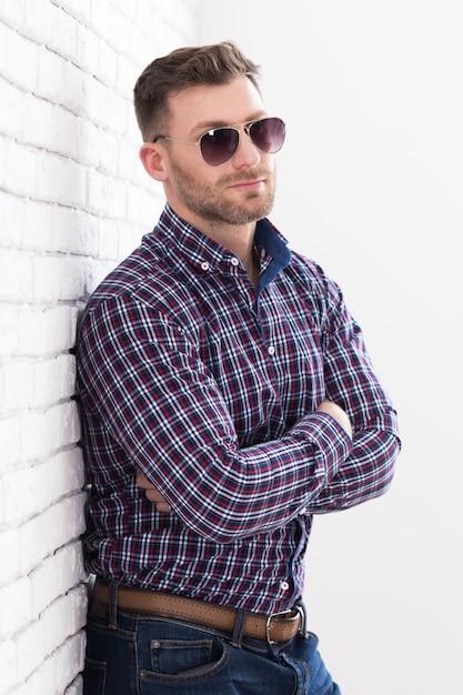 Homme brutal avec une barbe et des lunettes de soleil Photo Premium