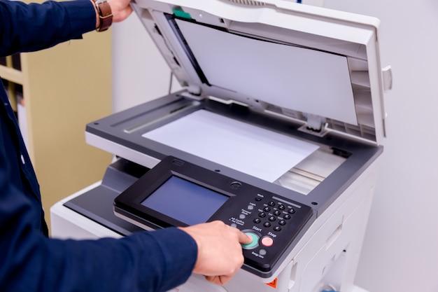 Homme de bussiness main appuyez sur le bouton sur le panneau de l'imprimante, imprimante scanner laser bureau copie machine fournit le concept de départ. Photo Premium