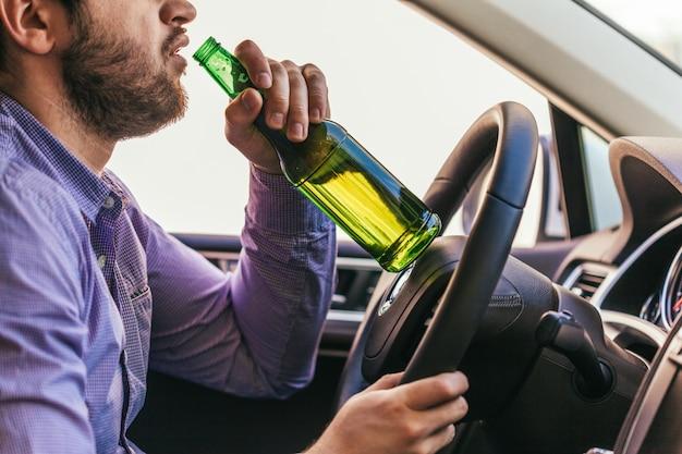 Homme buvant de l'alcool en conduisant la voiture Photo Premium