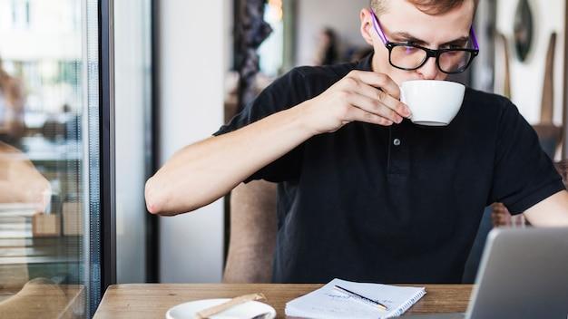 Homme buvant du café à la table avec un ordinateur portable Photo gratuit