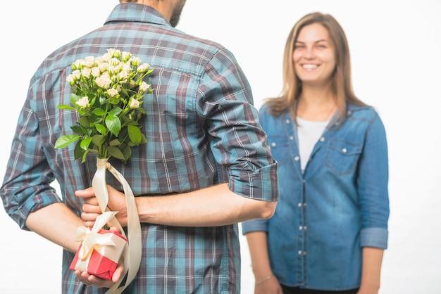 Homme cachant une boîte-cadeau et une fleur derrière son dos, surprenant sa petite amie Photo gratuit