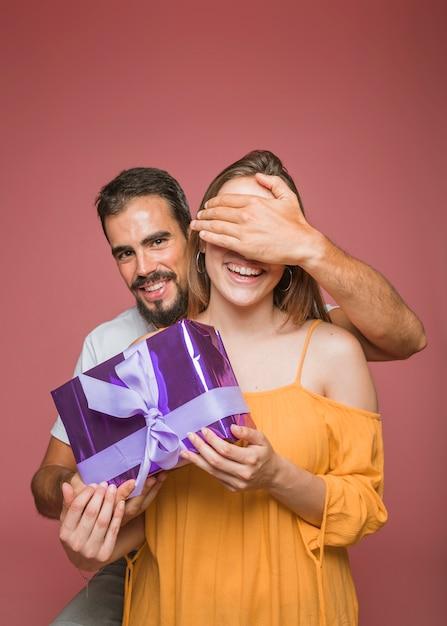 Homme cachant les yeux de sa petite amie tenant une boîte cadeau sur fond coloré Photo gratuit