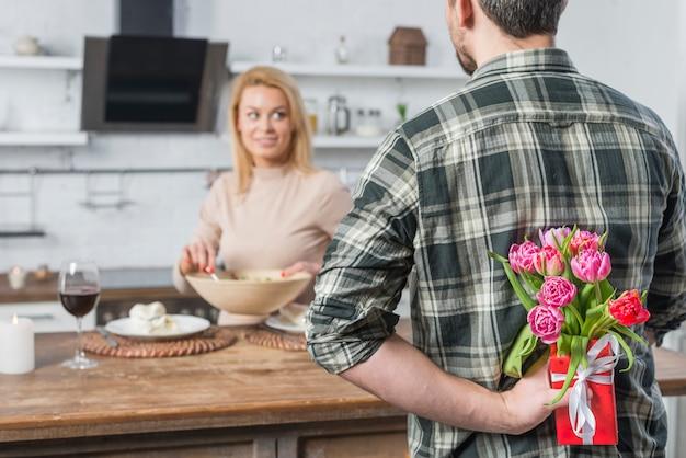 Homme avec cadeau et fleurs de dos et femme en cuisine Photo gratuit