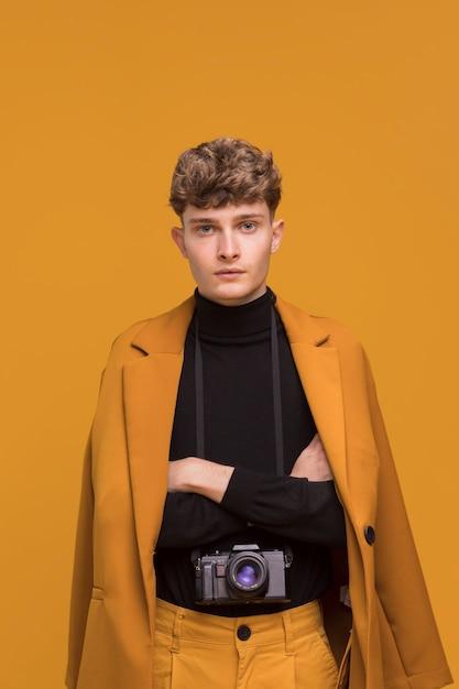 Homme avec une caméra dans une scène jaune Photo gratuit