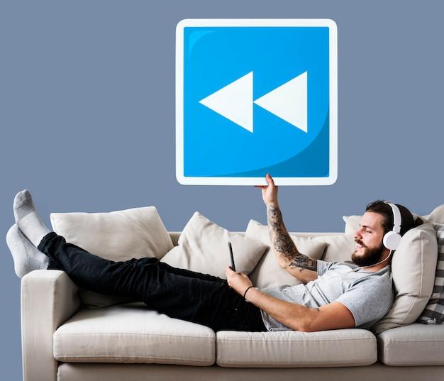 Homme sur un canapé tenant une icône de bouton de rembobinage Photo gratuit