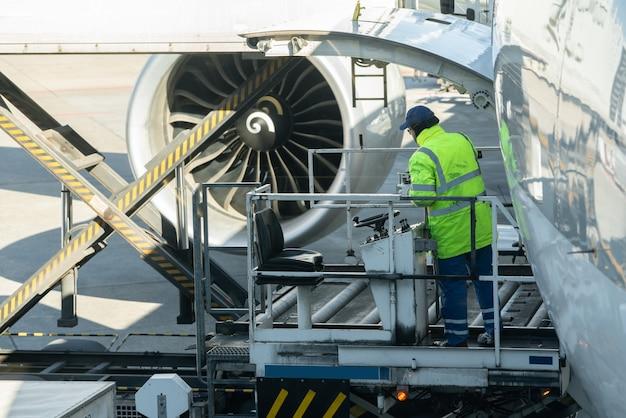 Un homme cargo sur une plate-forme de chargement charge du fret aérien à un avion cargo. Photo Premium