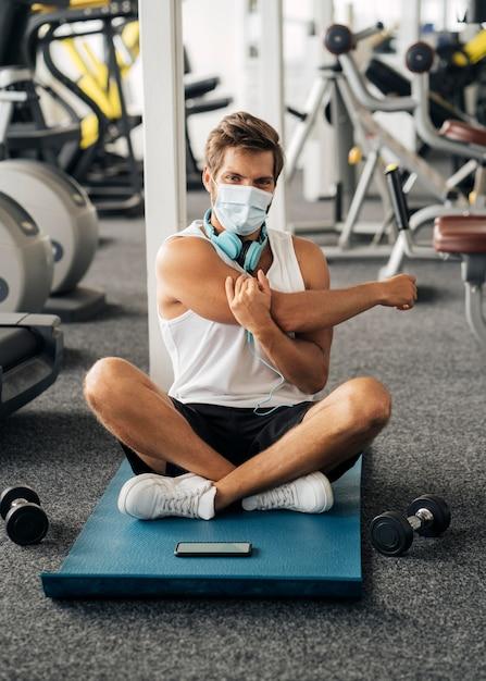 Homme Avec Un Casque Et Un Masque Médical à La Salle De Sport Sur Tapis Photo gratuit