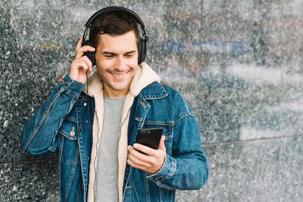 Homme avec casque et smartphone en milieu urbain Photo gratuit