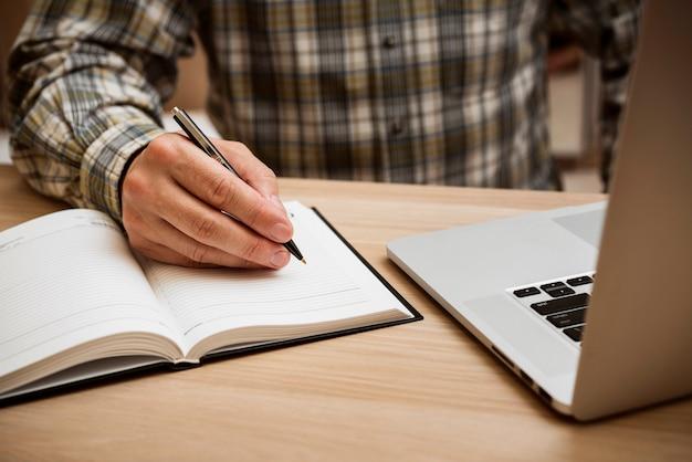 Homme casual écrit dans un cahier vierge Photo gratuit
