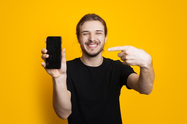 Homme Caucasien Aux Cheveux Longs Avec Barbe Pointant Vers Son Téléphone Avec De L'espace Libre Sur Le Mur Jaune Photo Premium