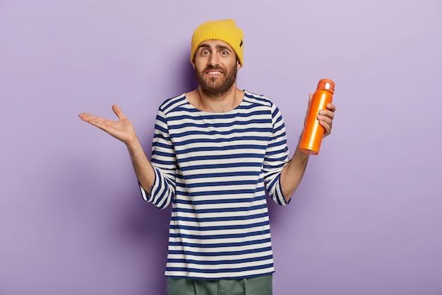 Un Homme Caucasien Confus Inconscient Soulève La Paume Avec Hésitation, Tient Une Fiole Orange Avec Une Boisson Chaude, Porte Un Chapeau Jaune Et Un Pull Rayé Photo gratuit