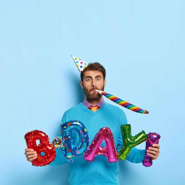 Homme Caucasien Drôle Souffle Dans La Corne De Fête Photo gratuit