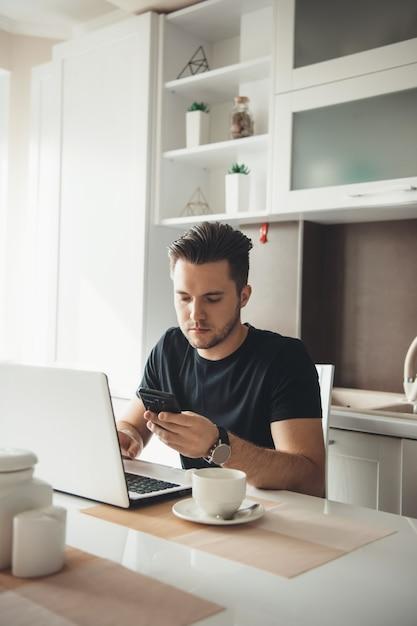 Homme Caucasien Occupé à Discuter Sur Mobile à La Maison Tout En Travaillant à L'ordinateur Portable Et En Buvant Un Café Photo Premium