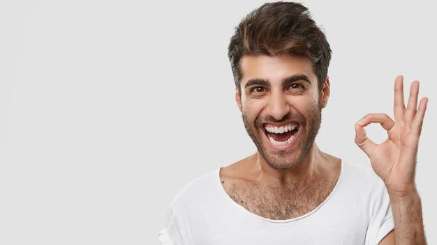 Un Homme Caucasien Positif Montre Un Signe Correct Ou Zéro, Sourit D'excitation, Se Sent Heureux Photo gratuit