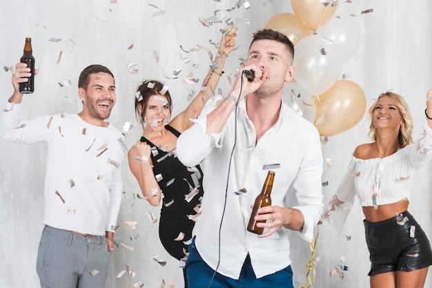 Homme chantant karaoké à la fête Photo gratuit