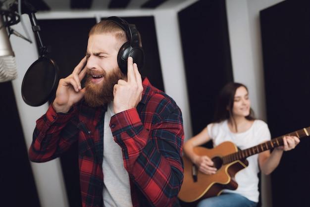 Un Homme Chante Et Une Femme Joue De La Guitare. Photo Premium