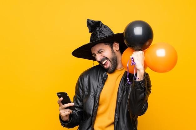 Homme avec chapeau de sorcière tenant des ballons à air noir et orange pour la fête d'halloween avec téléphone en position de victoire Photo Premium