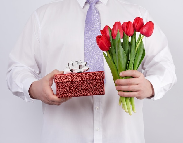 Homme En Chemise Blanche Et Cravate Lilas Tenant Un Bouquet De Tulipes Rouges Avec Des Feuilles Vertes Et Coffret Cadeau Photo Premium