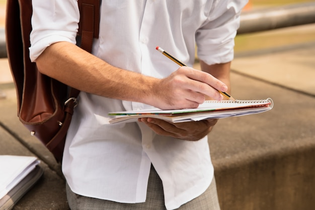 Homme en chemise blanche écrit avec un crayon sur papier Photo gratuit
