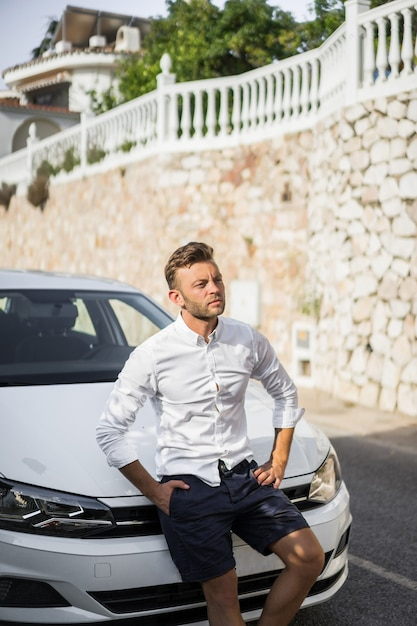 Un homme en chemise blanche est assis sur le capot d'une voiture. Photo gratuit