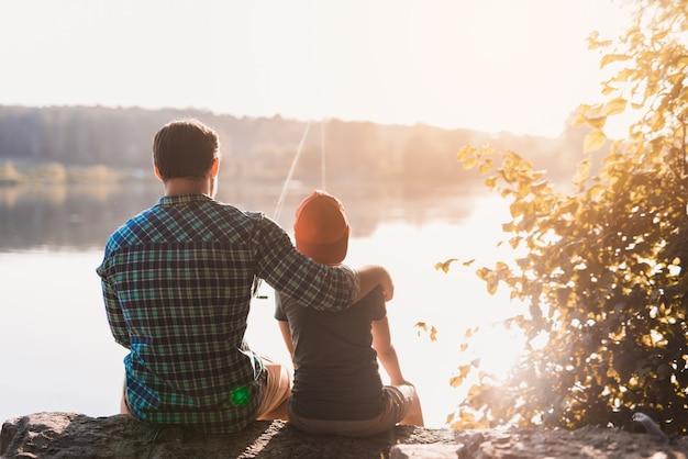 Un homme en chemise bleue est assis sur la rive du fleuve et serre son fils dans ses bras Photo Premium