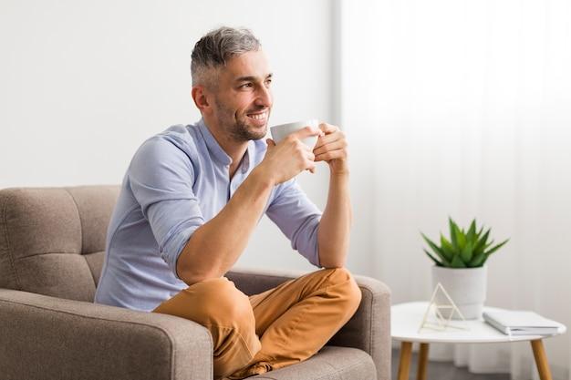 Homme En Chemise Bleue Tenant Une Tasse Blanche Et Des Sourires Photo gratuit