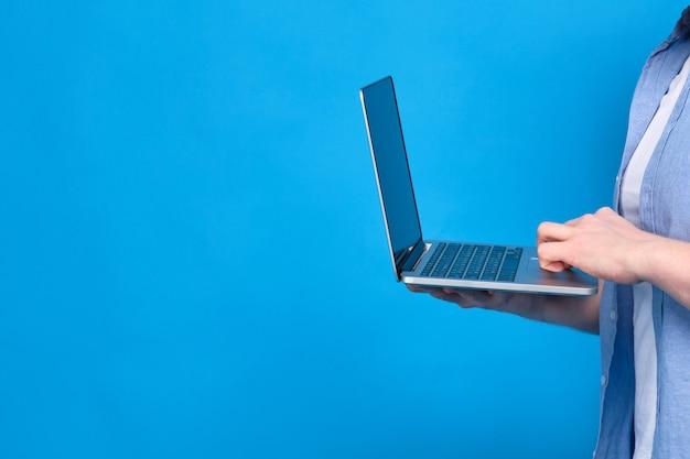 Un Homme En Chemise Bleue Tient Un Ordinateur Portable. Concept De Matériel D'apprentissage Des étudiants Sur Internet. Copiez L'espace. Photo Premium