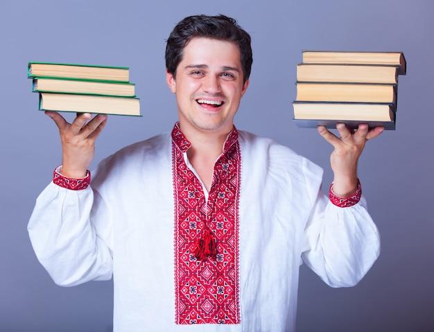 Homme en chemise de broderie avec des livres. Photo Premium