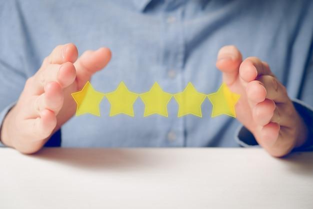 Un Homme En Chemise Montre Abstraitement La Cote Avec Ses Mains Cinq étoiles. Meilleur Score Photo Premium