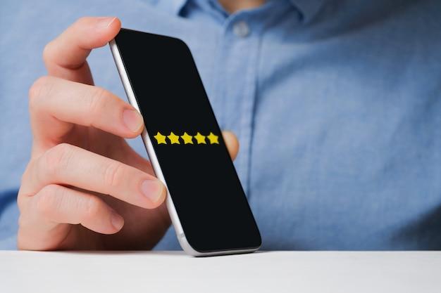 Un Homme En Chemise Montre Abstraitement Une Note De Cinq étoiles Dans Un Smartphone. Meilleur Score. Photo Premium