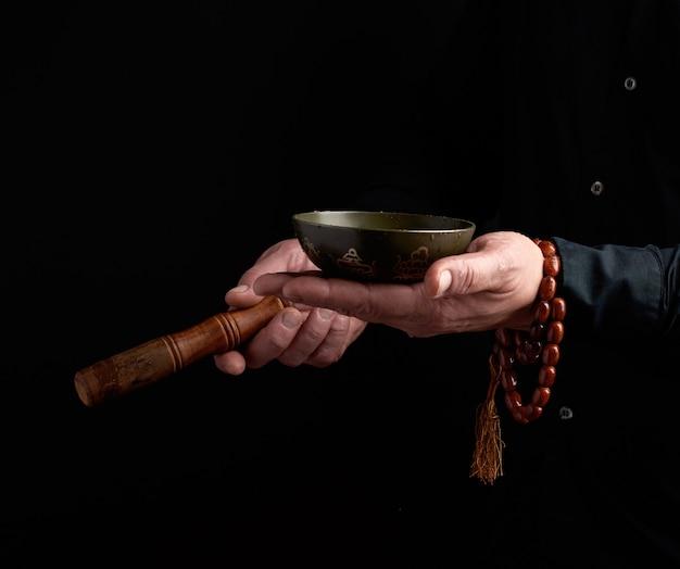 Un Homme En Chemise Noire Fait Tourner Un Bâton En Bois Autour D'un Bol Tibétain En Cuivre. Rituel De Méditation Photo Premium