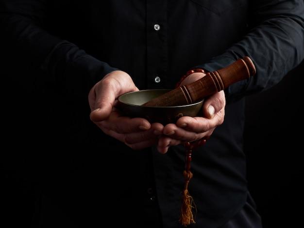 L'homme En Chemise Noire Tient Un Bol Chantant En Laiton Tibétain Et Un Bâton En Bois, Un Rituel De Méditation Photo Premium