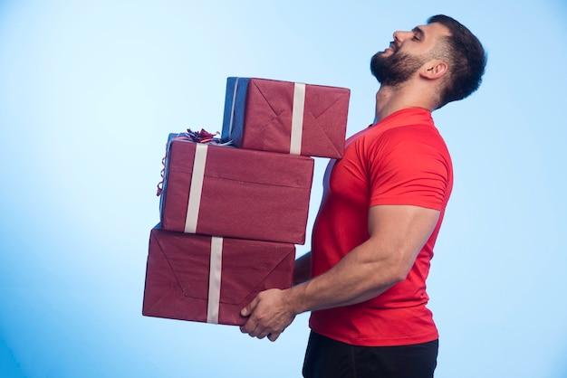 L'homme En Chemise Rouge Détient Un Stock De Coffrets Cadeaux Photo gratuit