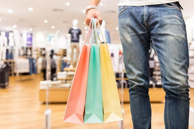 Homme chic avec sac à provisions en magasin Photo Premium