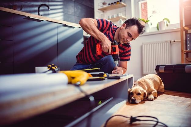 Homme Avec Chien Construisant Des Armoires De Cuisine Et à L'aide D'une Perceuse Sans Fil Photo Premium