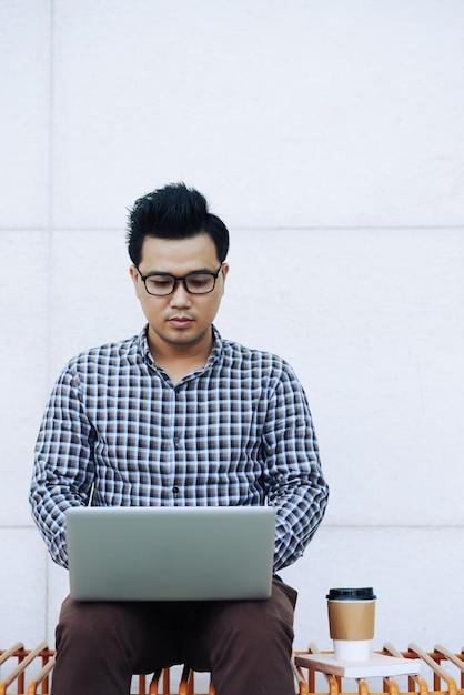 Homme Chinois Dans Des Verres Assis Sur Un Banc à L'extérieur Et à L'aide D'un Ordinateur Portable Photo gratuit