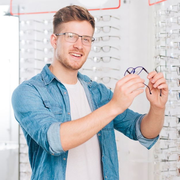 Homme Choisissant De Nouvelles Lunettes Chez L'optométriste Photo gratuit