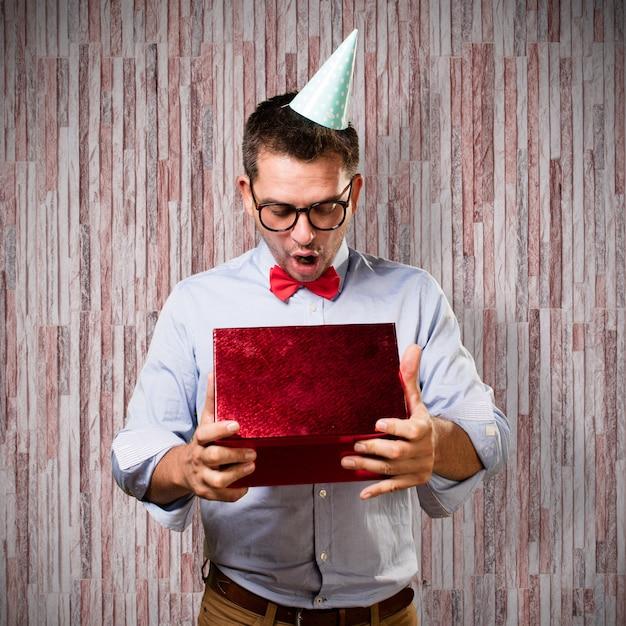 L'homme Coiffé D'un Chapeau Rouge Noeud Papillon Et Partie. Tenir Cadeau. Regarder S Photo gratuit