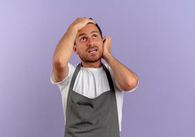 Homme De Coiffeur En Tablier à La Recherche Avec Une Expression Confuse Debout Sur Un Mur Violet Photo gratuit