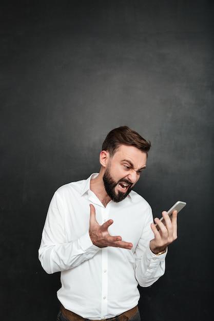 Homme En Colère Criant D'être Irrité Tout En Regardant Sur Smartphone Dans Sa Main Sur Gris Foncé Photo gratuit