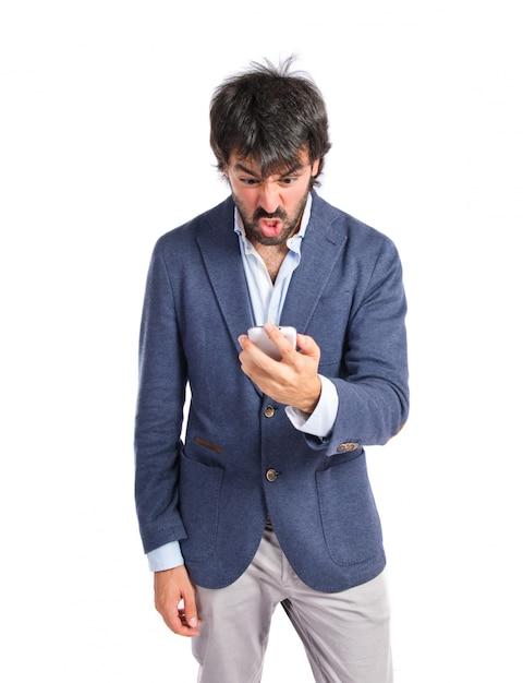 Homme en colère qui parle au mobile sur fond blanc Photo gratuit