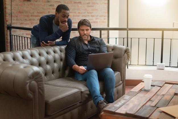 Homme, collègues, discuter, désinvolture, idées, sur, sofa, dans, lieu de travail moderne Photo Premium
