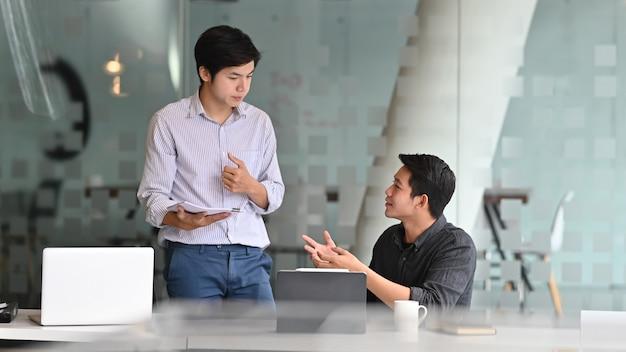 Homme de collègues parlant avec des documents dans le bureau moderne. Photo Premium