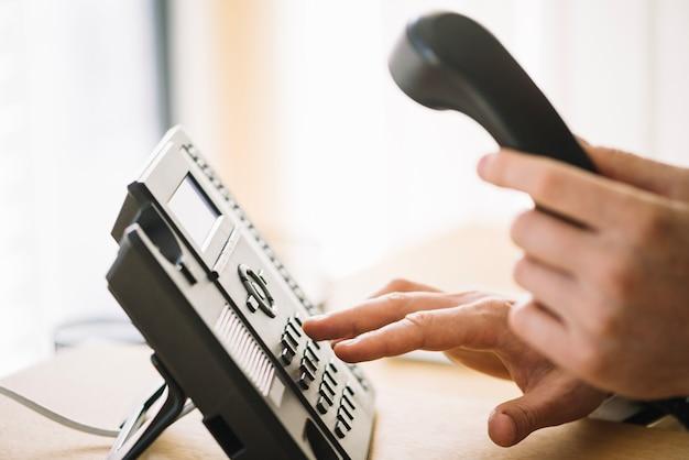 Homme en composant le numéro sur le téléphone Photo gratuit