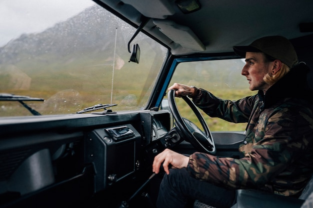 Homme conduisant un vieux suv dans les highlands Photo gratuit