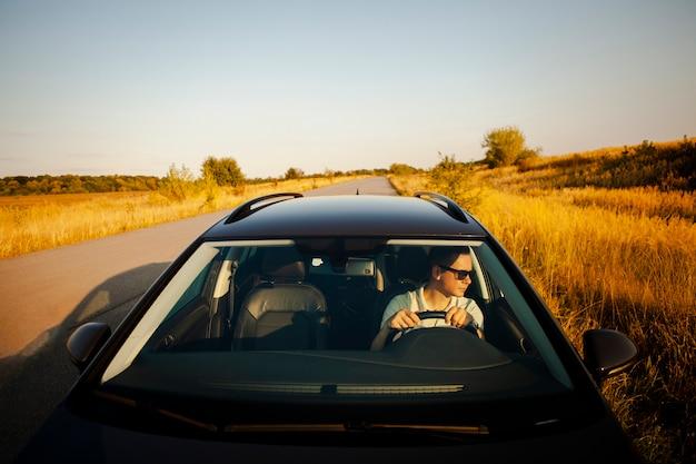 Homme conduisant une voiture noire Photo gratuit